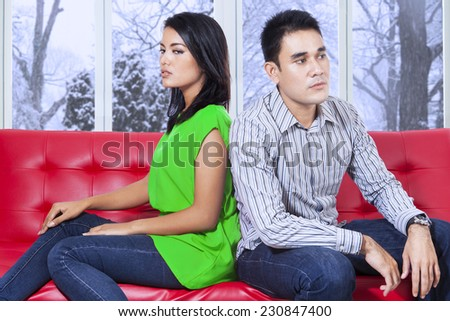 Young couple quarreling at home and sitting on sofa separately with mad expression - stock photo