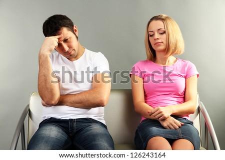 Young couple quarreling on grey background - stock photo