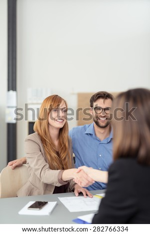 Young couple reaching an agreement with a broker or agent as the wife shakes her hand watched by a smiling husband - stock photo