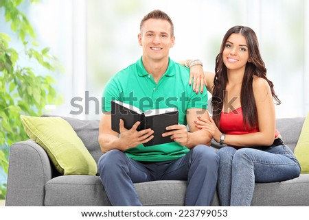 Young couple reading a book in the living room of their home