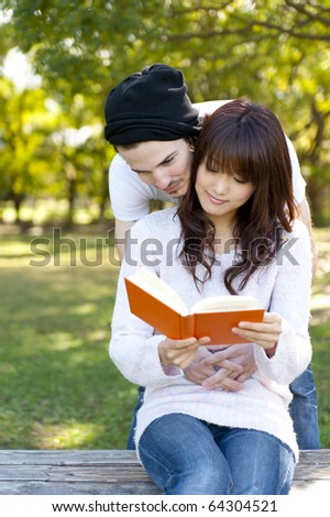 young couple reading a book on park bench