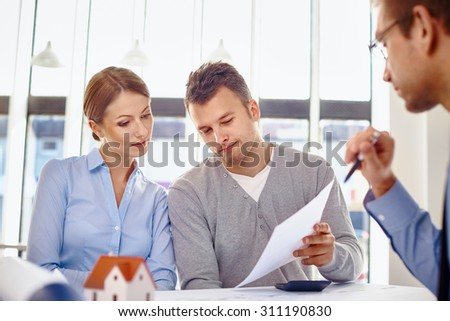 Young couple reading loan contract for new home - stock photo