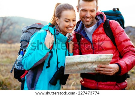 Young couple reading map during autumn backpacking, hiking. - stock photo