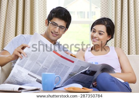Young couple reading newspaper together - stock photo