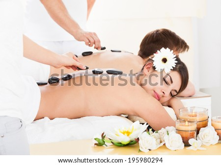 Young couple receiving Lastone therapy at beauty spa - stock photo