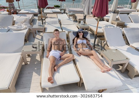 Young couple relaxing at a seaside resort lying sunbathing on comfortable recliner chairs in the tropical summer sun - stock photo