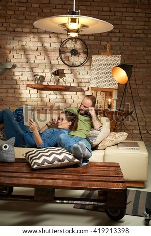 Young couple relaxing at home on sofa, using tablet computer.