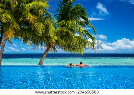 young couple relaxing in infinity pool under coco palms in front of tropical  landscape - stock photo