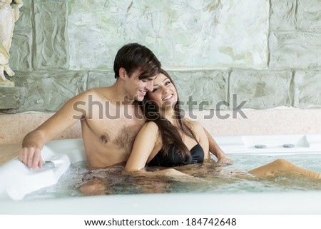 Young couple relaxing in the hot tub - stock photo