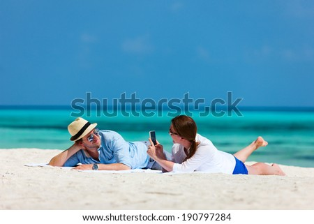 Young couple relaxing on a beach taking photos of each other during tropical vacation - stock photo