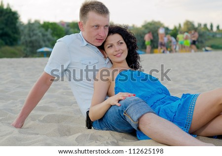 Young couple relaxing on a sandy beach with other beachgoers visible in the distance behind them
