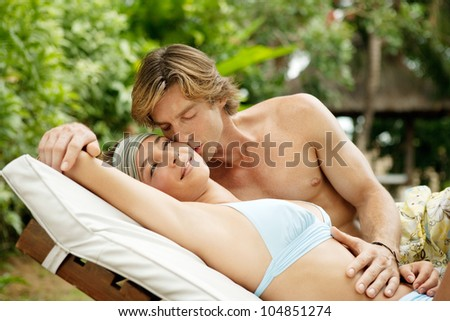 Young couple relaxing on a sun bed and kissing in a villa's tropical garden while on vacation. - stock photo