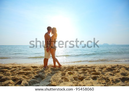 Young couple relaxing on a tropical beach at sunset - stock photo