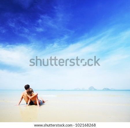 Young couple relaxing on a tropical sandy beach at sunny day
