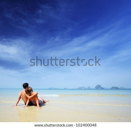 Young couple relaxing on a tropical sandy beach at sunny day - stock photo