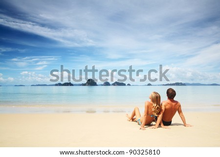 Young couple relaxing on a warm tropical sand