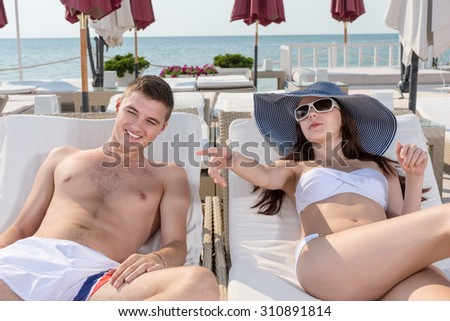 Young Couple Relaxing on Lounge Chairs While Having a Vacation in a Resort on a Tropical Climate. - stock photo