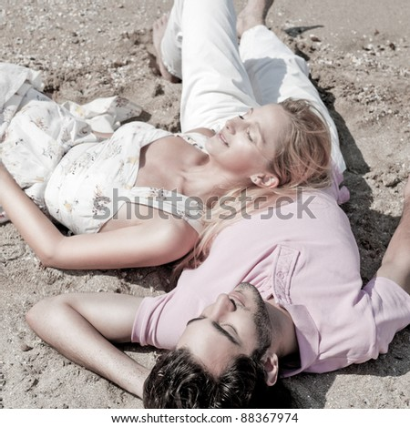 Young couple relaxing on sand at beach and daydreaming with their eyes closed - stock photo
