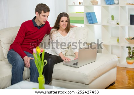 Young couple relaxing on sofa with laptop in the living room.Selective focus - stock photo