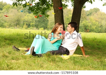 Young couple relaxing on the grass under a tree - stock photo