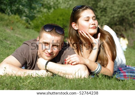 Young couple relaxing on the green meadow on the sunlight