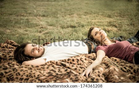 Young couple relaxing outdoor in nature (woman lies on man) - stock photo
