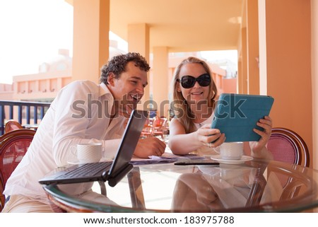 Young couple relaxing over coffee on a balcony sitting at a glass table smiling as they lean close together to read the screen on a tablet computer - stock photo
