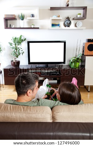Young couple relaxing, watching TV and having a beer - stock photo