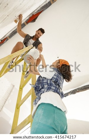 Young couple renovating home diy. Woman passing painting to man on top of ladder.