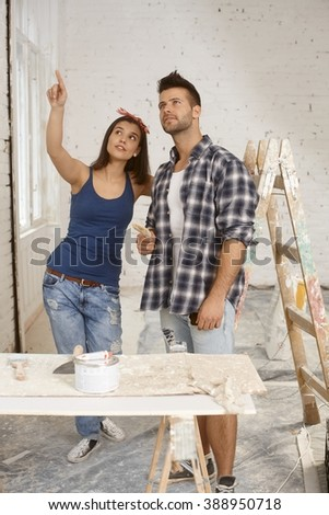 Young couple renovating home, talking, - stock photo