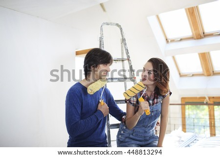 Young couple repairing the flat. Young woman and a man with rollers in them hands preparing to paint the wall.   - stock photo