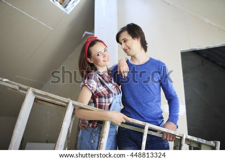 Young couple repairing the flat. Young woman and a man with stepladder in them hands preparing to paint the wall.   - stock photo