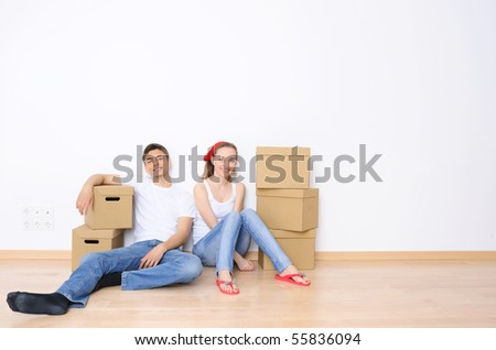 Young couple resting from moving into a new home. Great copy space.