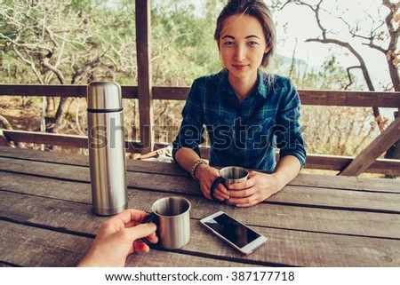 Young couple resting in summer arbor and drinking tea. Man looking at young woman, point of view