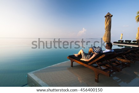 Young Couple Resting on Sun Loungers by swimming Pool - stock photo