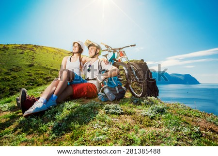 Young couple resting together on nature with the bike in the mountains. Youth sports. - stock photo