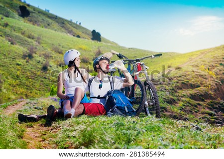Young couple resting together on nature with the bike in the mountains. Youth sports. Man drinks water from a bottle. - stock photo