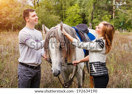 Young couple riding a horse at countryside at summer