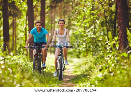 Young couple riding bicycles in natural environment - stock photo