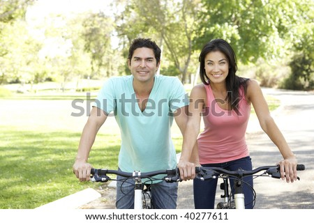 Young Couple Riding Bikes In Park - stock photo