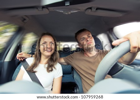 Young couple riding in a car - stock photo