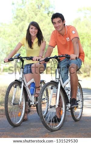 Young couple riding their bikes - stock photo