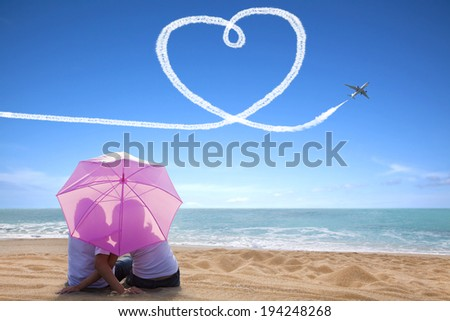 young couple romantic kissing at the beach with the umbrella - stock photo