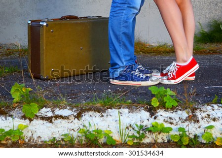 Young couple.Romantic meeting.Suitcase, jeans and sneakers.The photo is tinted in a retro style. - stock photo