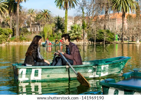 Young couple rowing small boat on city lake. - stock photo