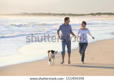 Young couple running along the beach with their dog.  - stock photo