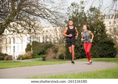young couple running in the park - stock photo