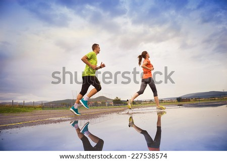 Young couple running on asphalt in rainy weather splashing in puddles. - stock photo