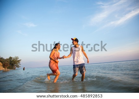 Young couple running on beach holding hands and laughing at sunset out to sea. The concept of love and fun, a date