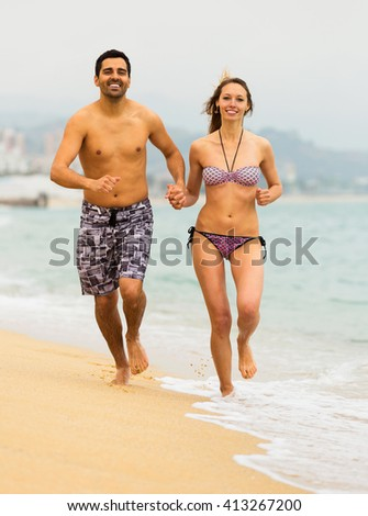 Young couple running together on the sea beach on vacation